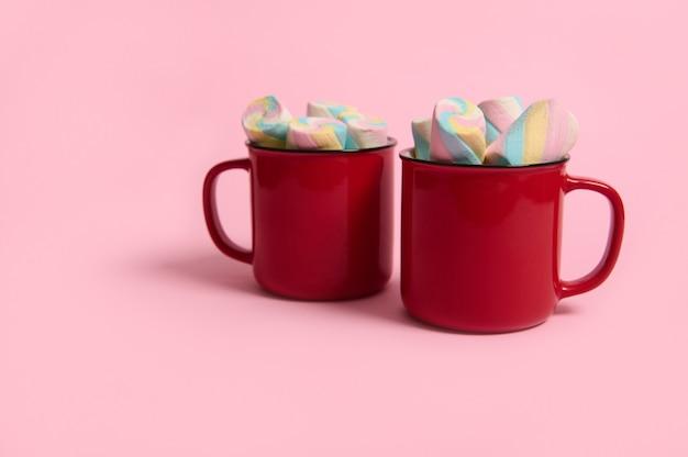 Студийная реклама выстрел красочных зефиров в красных чашках горячего шоколадного напитка, изолированных на розовом пастельном фоне с копией пространства для рождественской рекламы