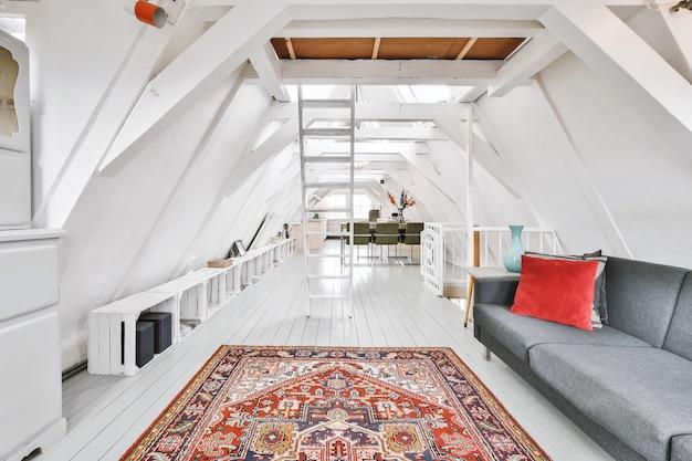흰 벽과 오픈 플랜 주방이있는 스튜디오 아파트와 거실에 소파가있는 다이닝 존