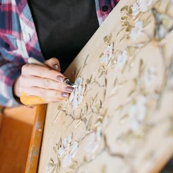 スタジオアートワーク。花柄の帆布。仕事中のアーティスト。モデリングツールの彫刻を持つ女性画家。