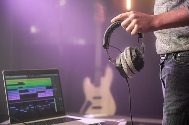 Студийные аудио наушники для записи звука в мужских руках на музыкальной студии