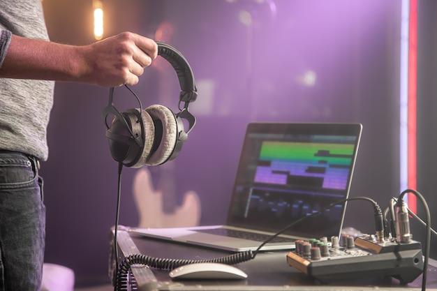 Studio audio headphones for recording sound in male hands on blurred studio background of music studio.