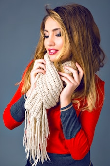 Studio autumn winter fashion portrait of beautiful stylish lady woman, wearing bright cashmere sweater, big cozy scarf, gray background.