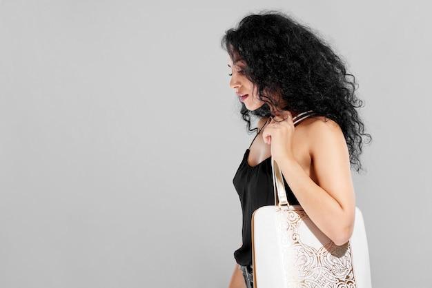 Крупный план студии красивой девушки с вьющимися черными волосами, несущей белую модную сумку с тиснением. она носит красивый черный топ и выглядит очень сексуально. фотография сделана на белом студийном фоне.