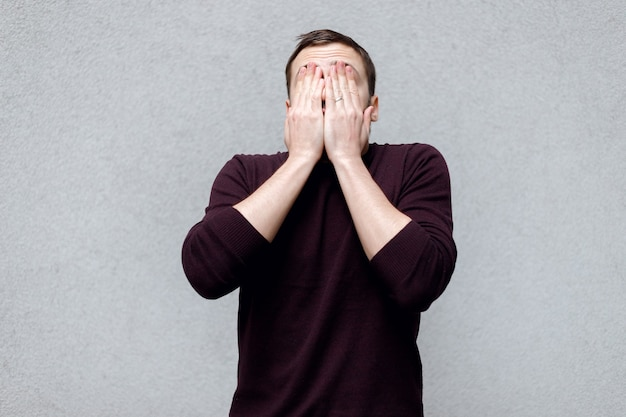 Studio close-up portrait of blond mature man covering his face with hands, not wanting to show your face, wanting to be anonymous, or being in anticipation of surprise. headshot over gray background