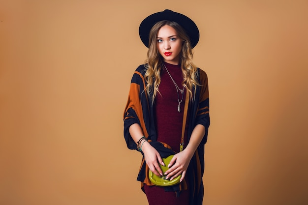 Studio close up portrait of young fresh blonde  woman in brown straw poncho , wool black trendy hat and round glasses looking at camera. green leather had bag.
