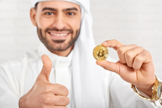 Studio close-up of a smiling arabian businessman keeps bitcoin and looks very happy
