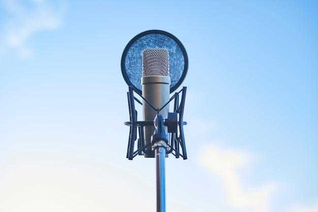 Студийный конденсаторный микрофон на фоне неба. скопируйте пространство.