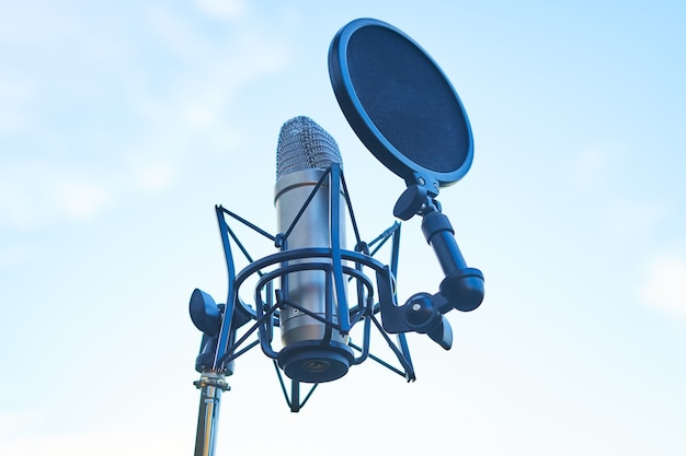 Studio condenser microphone on sky background. copy space.