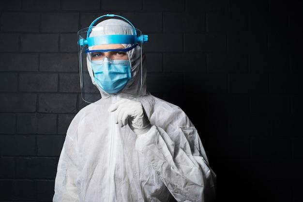 コロナウイルスとcovid-19に対してppeスーツを着ている若い医者の男のスタジオの暗い肖像画。黒レンガの壁の壁。手でフェイスシールドを保持します。