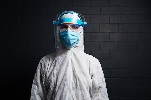 コロナウイルスとcovid-19に対してppeスーツを着ている若い医者の男のスタジオの暗い肖像画。黒レンガの壁の壁。