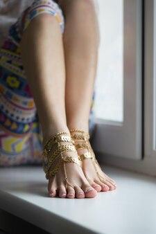 Студия детализировала снимок сексуальных красивых подошв женских ног с украшениями для ног на белом подоконнике
