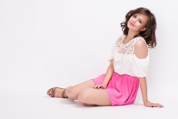 Studio fashion portrait of beautiful young woman, sitting,