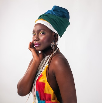Studio fashion portrait of young african woman in summer dress and ethnic head wrap