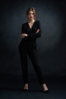 Studio frontview of young confident woman wearing black stylish suit and posing in front of camera.
