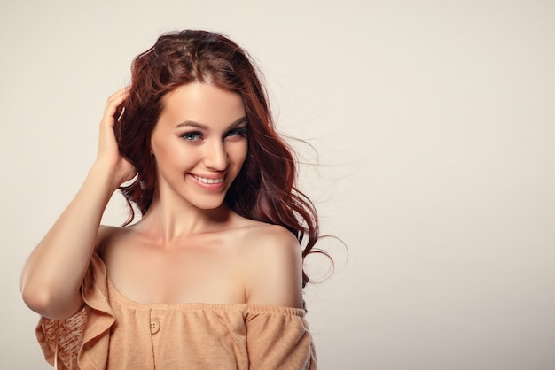 Studio glamor portrait of a beautiful woman with luxurious hair on a light background. place for copyspace.
