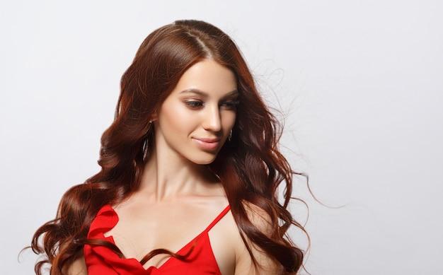 Студийный гламурный портрет красивой женщины с роскошными волосами на светлом фоне.