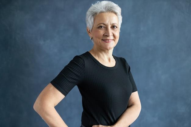 Immagine dello studio di donna di mezza età attraente allegra con capelli grigi pixie alla moda che sorride alla macchina fotografica, esprimendo emozioni positive.