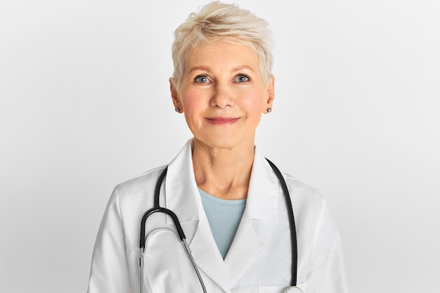 Studio image of confident attractive middle aged female doctor with short dyed hairstyle posing isolated wearing white coat and stethoscope.