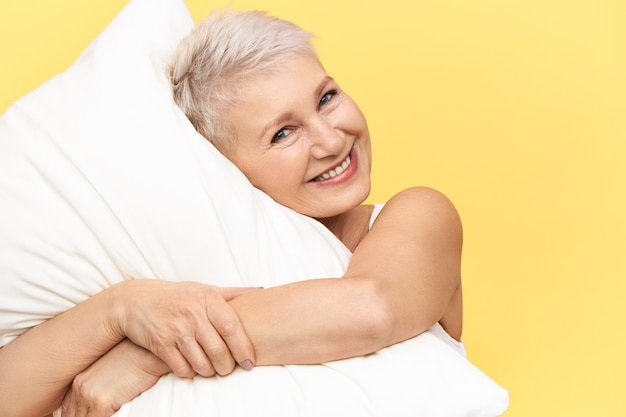Studio image of cute charming middle aged female hugging white down pillow, going to sleep, having happy cheerful facial expression.