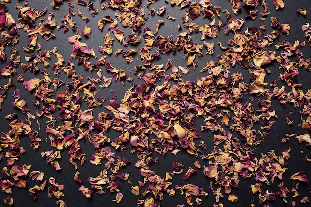 Studio image of dried tea rose leaves, on the dark background.