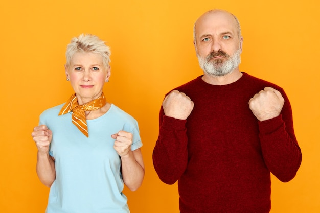 Studio image of elderly couple standing next to each other expressing negative emotions, being angry with high prices or low pension payments, clenching fists, having mad furious facial expression