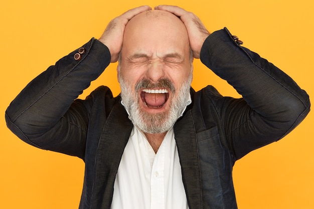Studio image of enraged devastated elderly businssman in formal clothes closing eyes and screaming out loud, loosing temper, keeping hands on his bald head, stressed because of business failure