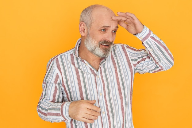 Immagine dello studio dell'uomo con la barba lunga calvo senior frustrato perplesso che tiene il palmo sulla fronte per proteggere gli occhi dal sole, esaminando la polvere o cercando qualcosa.