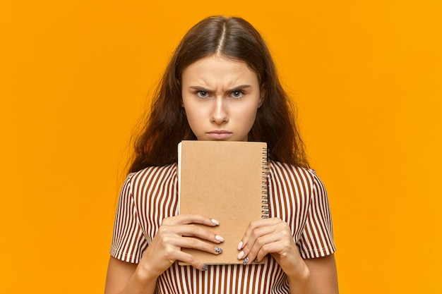 Studio image of grumpy female teenager with long loose hair holding diary at her face