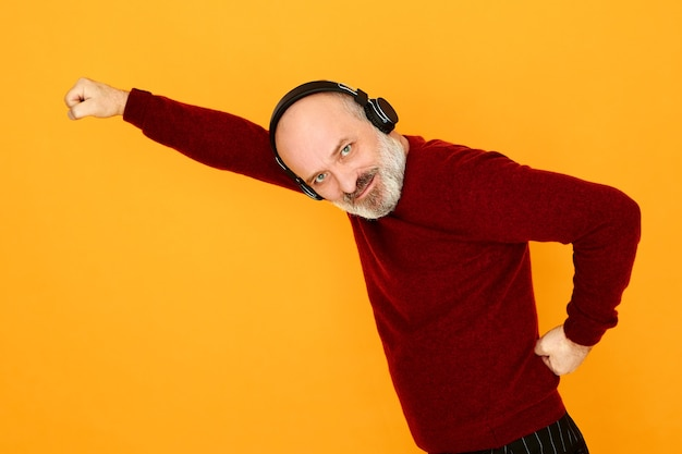 Studio image od energetic active bearded european male pensioner using bluetooth wireless earbuds listening to electronic music. elderly man enjoying perfect sound via headphones, having fun