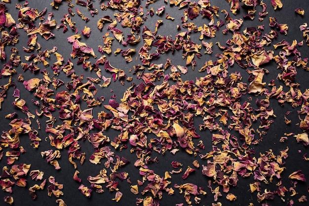 Студийное изображение сушеных листьев чайной розы на темном фоне.