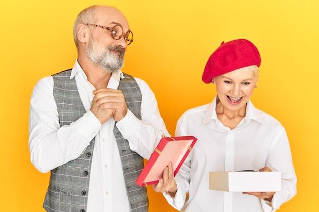 灰色のひげと禿げた頭を持つ感情的なエレガントな男性年金受給者のスタジオ画像は、彼からのプレゼントで魅力的な女性のオープニングボックスを見ています。贈り物を受け取る興奮した成熟した女性
