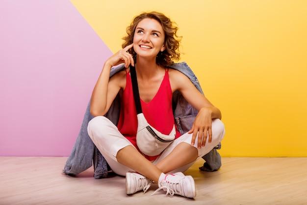 床に座ってスタイリッシュなスポーティな服とジーンズのジャケットを着て笑顔ブルネット素敵な女性のスタジオ画像。