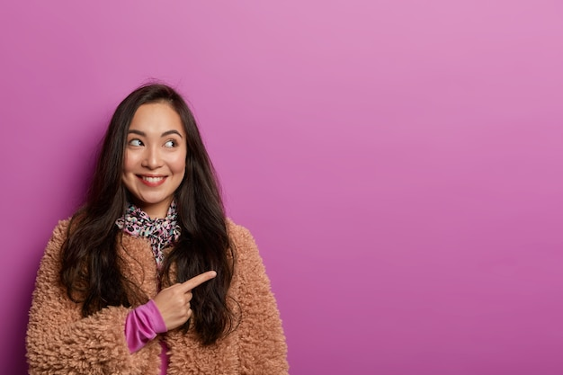 Studio image of positive asian lady points away on copy space, recommends visit shop where she bought new clothes for winter
