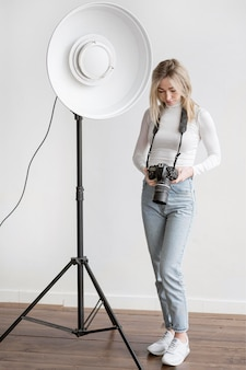 Studio lamp and woman holding a camera photo