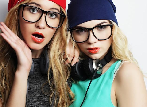 세련 된 밝은 의상, 모자, 데님 반바지 및 안경을 착용하고 미쳐 가고 함께 즐거운 시간을 보내고있는 두 명의 가장 친한 친구 힙 스터 소녀의 스튜디오 라이프 스타일 초상화. 젊음과 아름다움.