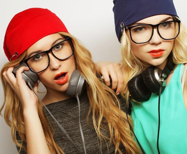 세련된 밝은 의상, 모자, 데님 반바지, 안경을 쓴 두 명의 가장 친한 힙스터 소녀의 스튜디오 라이프스타일 초상화가 미쳐가고 함께 즐거운 시간을 보내고 있습니다. 젊고 아름다움.