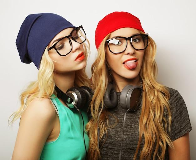 スタイリッシュな明るい衣装、帽子、デニムのショートパンツ、メガネを身に着けて、夢中になって一緒に素晴らしい時間を過ごしている2人の親友のヒップスターの女の子のスタジオライフスタイルの肖像画。若くて美しさ。