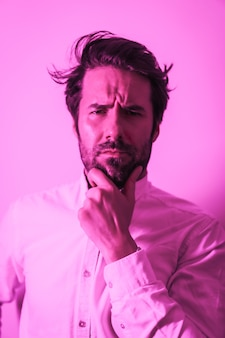 Studio lifestyle, portrait of a serious caucasian young man in a white shirt, illuminated with a pink neon light