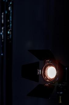 Прожектор студийного освещения. на темном фоне светит теплый сценический прожектор. старинный светильник с жалюзи. вертикальное фото с местом для лейбла или логотипа