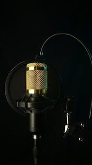 Студийный микрофон и поп-фильтр на черном фоне фото