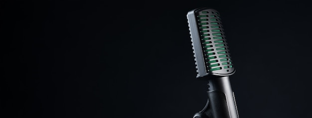 Studio microphone on black wall, close up