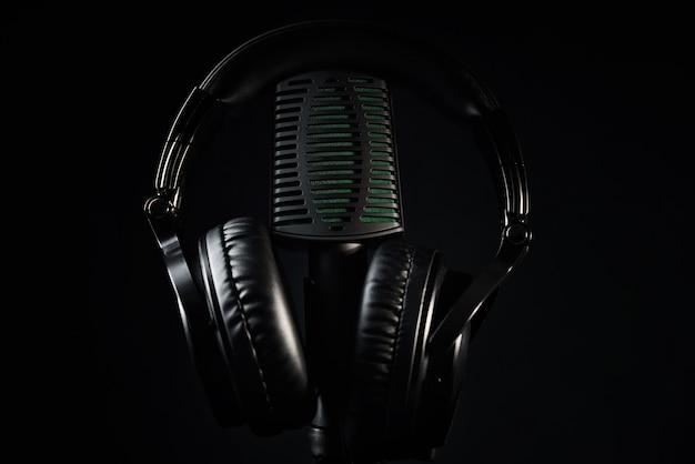 Studio microphone and headphones on the black background