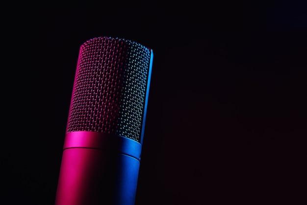 ネオンライト付きの暗い背景のスタジオマイク