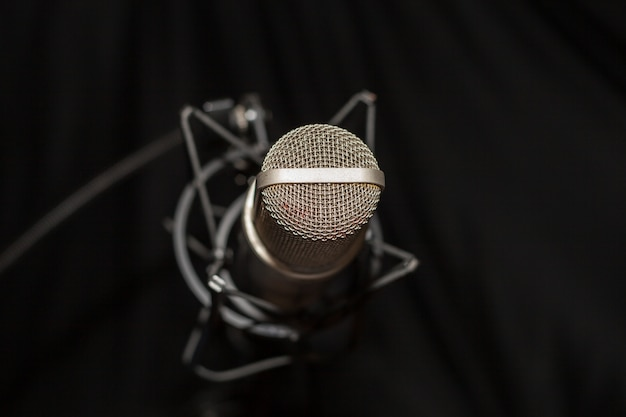Studio microphone on recording and black background