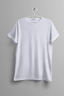 洋服のスタジオモックアップ。灰色の背景に影付きのプラスチックハンガーにぶら下がっている白いtシャツ。テンプレートはあなたのデザインに使用できます。