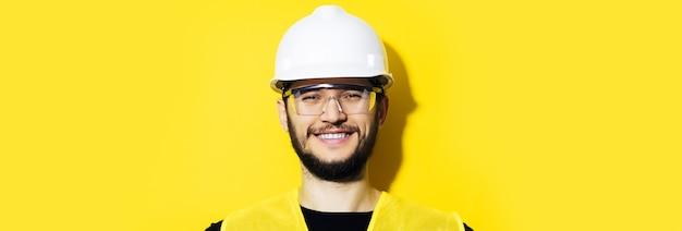 Студийный панорамный портрет молодого улыбающегося инженера-строителя рабочего человека в защитном шлеме и очках