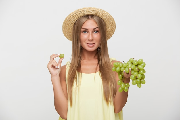 Studio photo of beautiful young blonde woman with natural makeup raising eyebrow while looking at camera and holding bunch of grapes while standing over white background