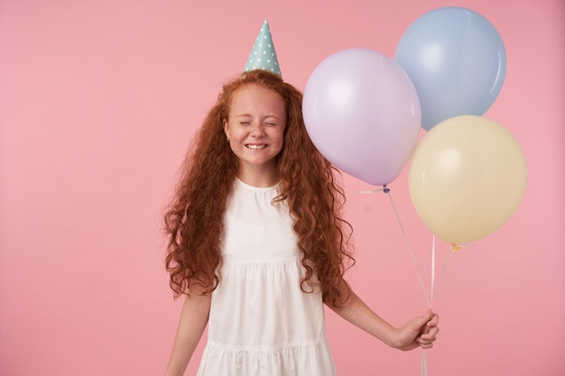 Studio photo of charming redhead female kid with long curly hair celebrates holiday, posing over pink background in festive clothes and birthday cap, smiling happily with closed eyes