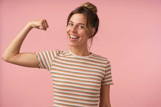 Studio photo of charming young brunette female dressed in beige striped t-shirt raising hand while demonstrating her power and smiling gladly at camera, isolated over pink background
