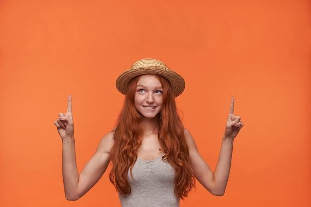 Studio foto di affascinante giovane dai capelli rossi donna in maglia grigia e cappello di paglia in piedi su sfondo arancione, guardando verso l'alto con gli indici sollevati e mordere underlip